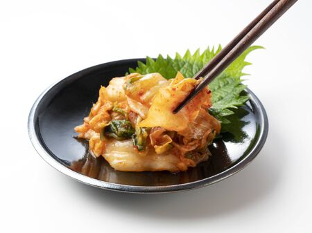 Kimchi in a plate set on a white background is lifted with chopsticks.
