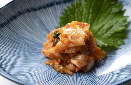 Diagonal view of kimchi in a plate on a white background.