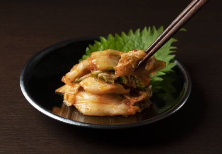 Kimchi in a plate set against a dark wooden backdrop is lifted with chopsticks.