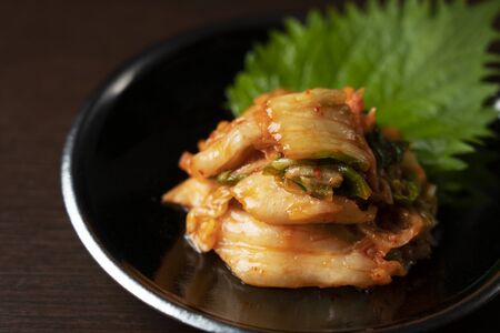 Kimchi on a plate set against a dark wooden background.