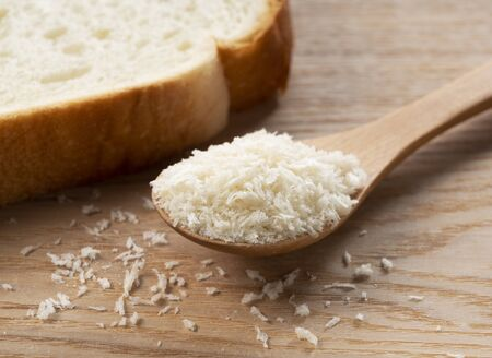 Crumbs and bread in a wooden spoon set against a wooden background.