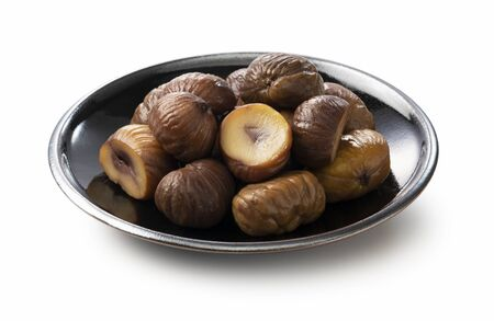 Peeled sweet chestnuts in a plate on a white background Zdjęcie Seryjne