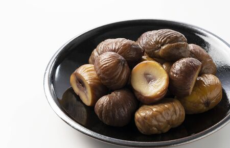Peeled sweet chestnuts in a plate on a white background