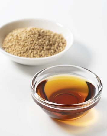 Sesame oil and sesame seeds on a white background Stock Photo