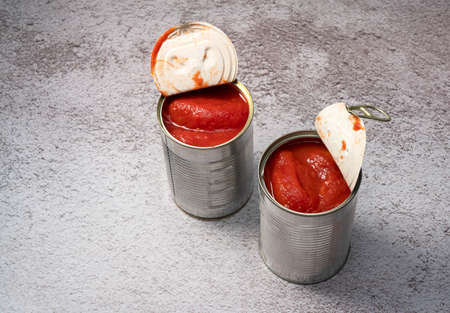 Whole tomato cans on a stone background