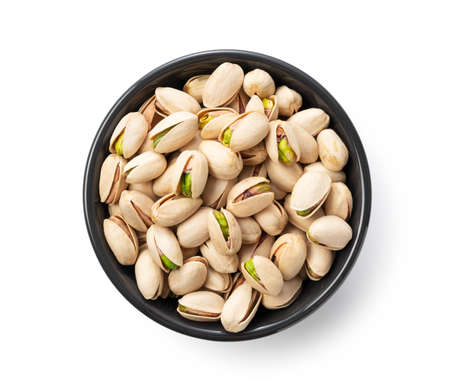 A bird's-eye view of the pistachios in a bowl set against a white background