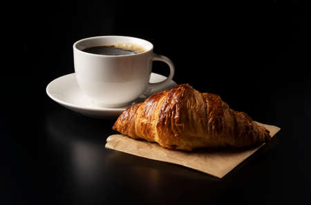 One croissant and hot coffee placed on a black background