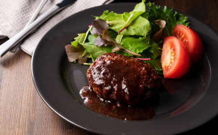 Hamburger with demi-glace sauce served on a plate placed on the table