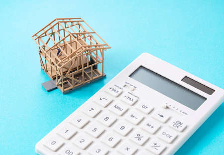 A model of a house and a calculator on a blue background. Business image