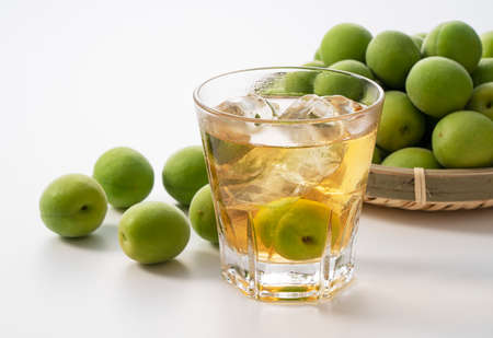 Japanese plum wine and unripe plums on a white background. Stock fotó