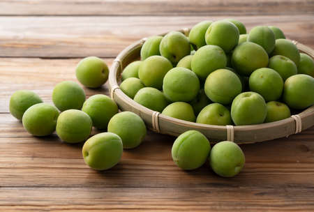 Unripe plums in a bamboo colander placed in the wooden background. Japanese apricot fruit. Stockfoto