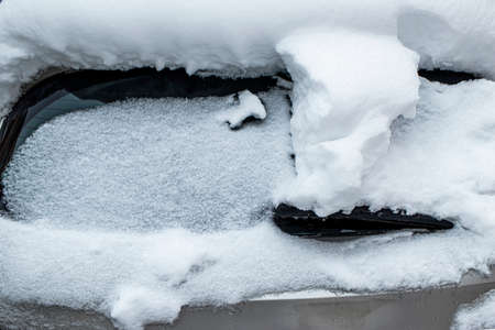 Snow-covered frozen car covered with snow. Winter road. Danger of winter driving. Car snow removal. Dangerous traffic situation.