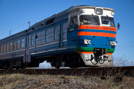 A commuter train moves on rails. Stock Photo
