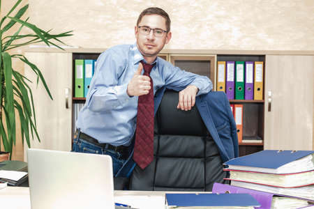 Boss businessman at his desk in the office. Leans with his hand on the back of the bracket on which the jacket hangs. The gesture is a raised thumb. Successful office worker. Successful career