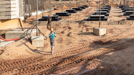 A worker transfers elements for the installation of the formwork at the construction site. Monolithic concrete formwork during the construction of a residential building