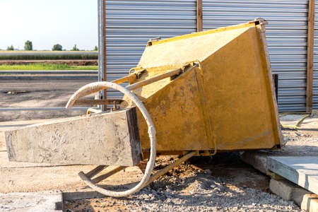 Cone tank for conveying and pouring concrete in monolithic construction by crane. A capacity for transporting concrete. Reinforced concrete monolithic work at the construction site