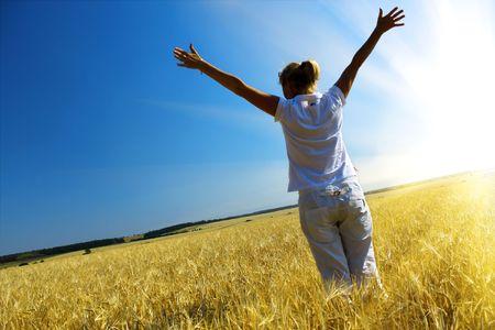 Woman in wheaten field and beautiful sunset photo