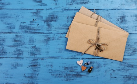 parting the sea: Expectation concept. Envelopes and small hearts on blue wooden texture