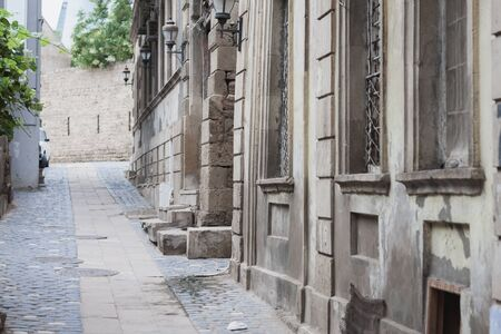 baku: Narrow streest of Old City Baku with grape leaves and old stone buildings Stock Photo