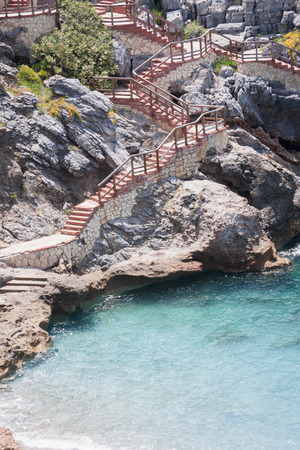 Stairs built on rocks descending to beach with turquoise water