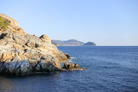 greece granite: Mountains and blue sea with rocks in sharp focus and blurred mountains on background Stock Photo