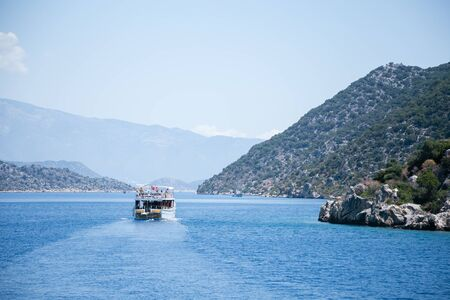 UCHAGIZ SIMENA, TURKEY - MAY 20: bay of Uchagiz village in Antalya province of Turkey with mountains covered by evergreen bushes shut on sunny day with one turistic boat with Turkish flag in 2016 Stock Photo
