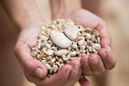 Close up of woman hands holding pebble of mixed white biege and terracotta color shot on Kaputash beach of Turkey with focus on pebble and palms blurred and blurred background