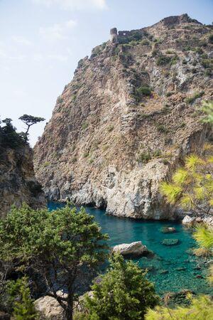 Beautiful Delik Deniz sea bay with pristine waters and  remains of medieval castle on top of rock in Guney koyu village of Gazipasha Alanya Turkey near historical site Antiochia ad Cragum. Stock Photo