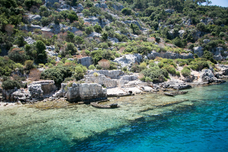 sunken city of Kekova in bay of Uchagiz view from sea in Antalya province of Turkey with turqouise sea rocks and green bushes with remains of ancient city visible under water