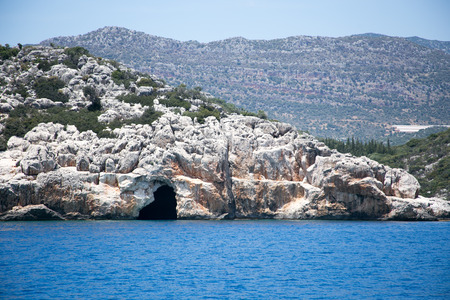 Sea cave in bay of Uchagiz in Mediterranean Turkey with blue sea and mountains blurred on background Stock Photo