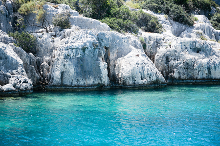 the sunken: sunken city of Kekova in bay of Uchagiz view from sea in Antalya province of Turkey with turqouise sea rocks and green bushes