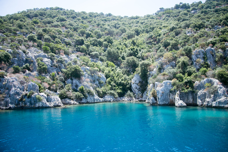sunken city of Kekova in bay of Uchagiz view from sea in Antalya province of Turkey with turqouise sea rocks and greepn bushes