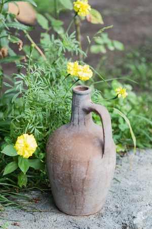 Decorative brown rustic clay jug and yellow flowers over blurred background