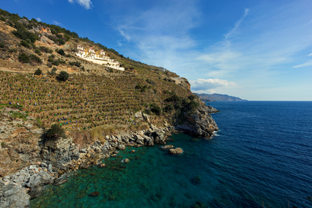 stiff slopes of mountains descending into sea with three villas overlooking seascape shot on sunny day