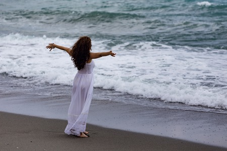 Woman wearing white maxi dress and enjoying  sea storm with arms spread 版權商用圖片