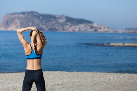 Healthy and fitness lifestyle Backview portrait of young woman wearing gym clothing stretching arms and exercising by seaside with sea and Alanya castle background Portrait layout. Stock Photo