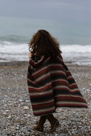 Backview portrait of happy brunette woman by seaside wearing striped red black and beige poncho