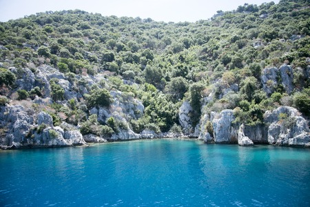 the sunken: sunken city of Kekova in bay of Uchagiz view from sea in Antalya province of Turkey with turqouise sea rocks and greepn bushes