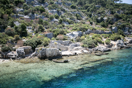 the sunken: sunken city of Kekova in bay of Uchagiz view from sea in Antalya province of Turkey with turqouise sea rocks and green bushes with remains of ancient city visible under water