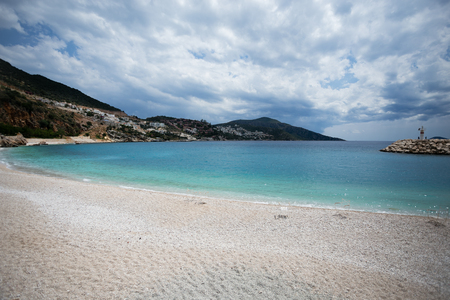 municipal beach of Kalkan resort town of Turkey located on Mediterranean sea with turquoise sea mountains and residential complexes on background and sky with clouds Stock Photo
