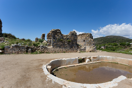 afrodita: Ancient pool in historical and archeological Antiochia ad Cragum site with pool in sharp focus and ancient walls slighly blurred and moutains blurred shot on sunny day.