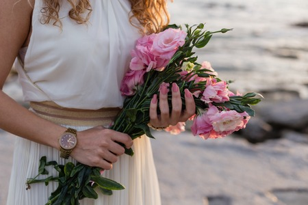 Woman hands holding bouquet of pink eustoma with blurred sea in background