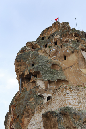 Upper part of Ortahisar castle in Cappadocia with caves carved in rock formation shot against blue sky with clouds