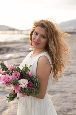 floristry: Beautiful woman with wavy hair wearing white dress and holding bouquet of pink lisianthus Stock Photo