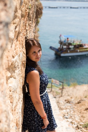 Woman with straight brown hair wearing dark blue dress with blurred sea os background and ship