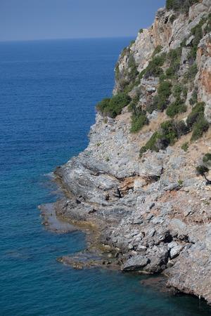Vertical shot of steep slopes descending to the blue sea