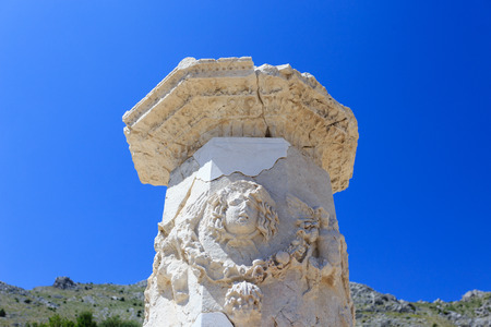 Carved marble column in agora of ancient city of Sagalassos with agora on background