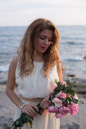 Potrait layout image of beautiful lady smiling and wearing sleaveless ivory dress and holding bouquet of pink eustoma flowers with blurred sea in background