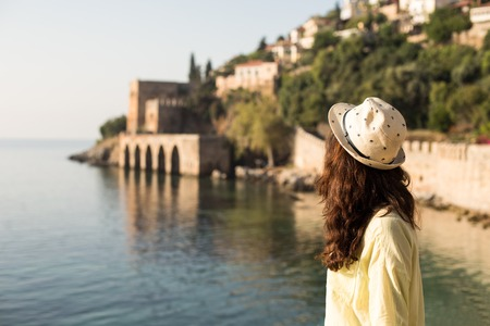 skirts: Horizontal backview portrait of a traveller woman with brown wavy hair wearing beige hat  and yellow cotton shirt enjoying the seaview and view of Mediterranean shipyard in Alanya, Turkey. Stock Photo