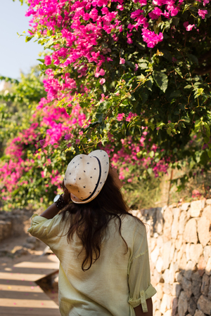 skirts: Backview portrait of a traveller woman with wearing yellow shirt and beige hat and looking at blossoming bouganvilea Stock Photo
